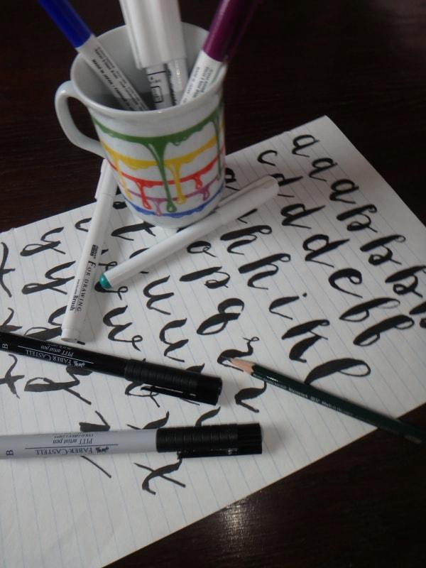 stránka s kreativním písmem a fixy na psaní