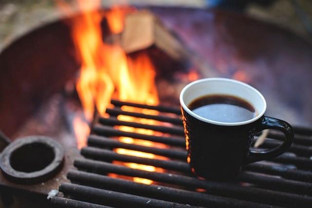 oheň a na roštu hrnek s kávou na zahřátí