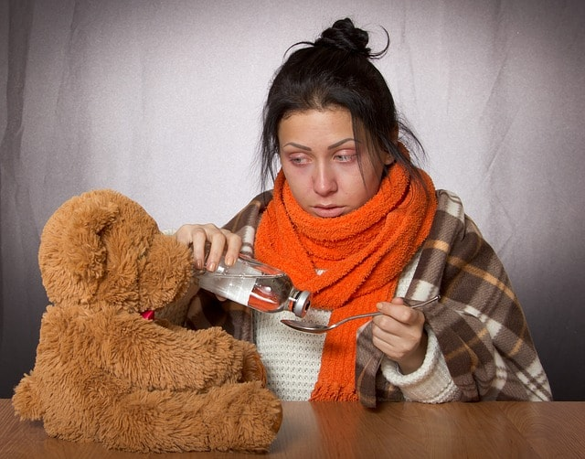 žena s chřipkou dává lék medvídkovi